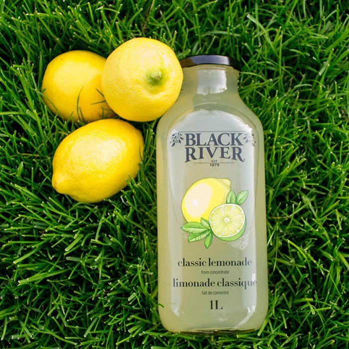 Black River classic lemonade in a 1 litre glass bottle with green grass and 3 lemons