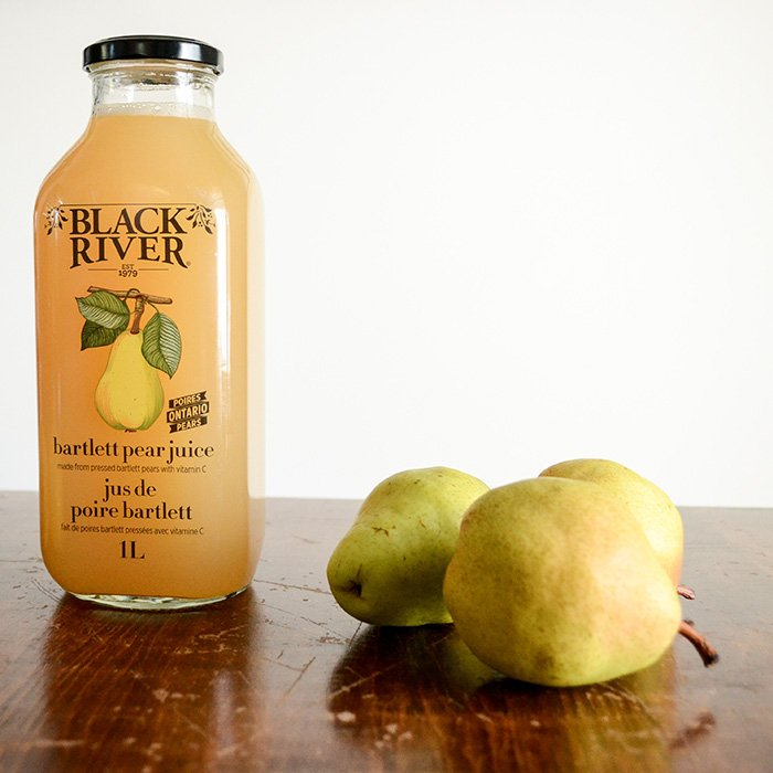 Black River Bartlett Pear Juice on a wood table with Bartlett Pears