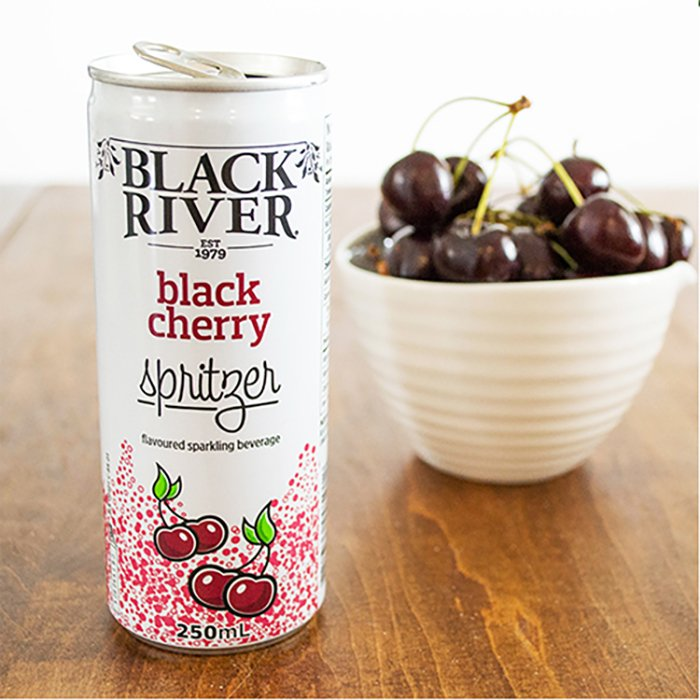 Black River black cherry spritzer on a table and cherries in a bowl